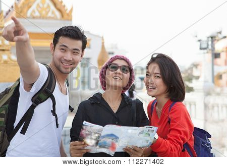 Traveling Man Woman And Senior Tourist Holding Travel Guide Book In Hand Pointing To Destination For