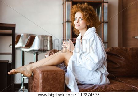 Attractive thoughtful young woman with curly red hair in white bathrobe sitting on brown sofa