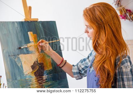 Beautiful serene young female painter with long red hair painting picture on canvas in art workshop