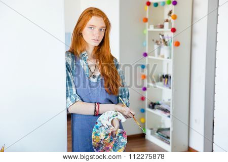 Portrait of beautiful young redhead woman painter with art palette and brush in art workshop