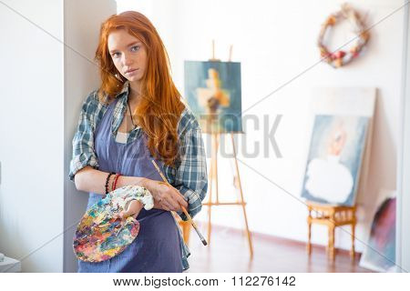 Thoughtful atractive young woman painter with long red hair in apron holding art palette and brush in artist workshop