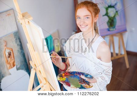 Cheerful pretty young woman artist standing and painting picture in artist workshop