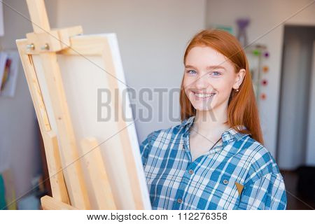 Pretty cheerful young woman painter in checkered shirt painting in art studio