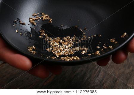 Hands holding a black plate with gold nugget grains, close-up