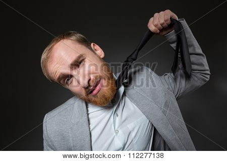 Hopeless stressed businessman with beard in grey suit hanging himself on tie over grey background