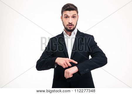 Handsome astonished young business man with beard in black suit pointing on watch over white background