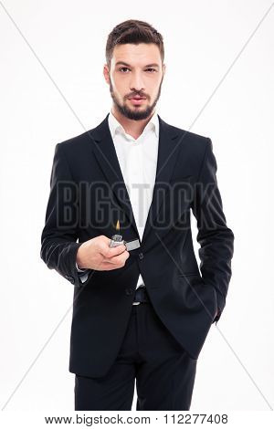 Confident bearded young business man in black suit and white shirt standing and holding gas lighter over white background
