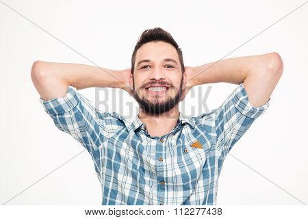 Carefree happy young bearded man in checkered shirt with hands behind head over white background