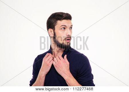 Scared dazed handsome young man with beard in sweetshirt looking away over white background