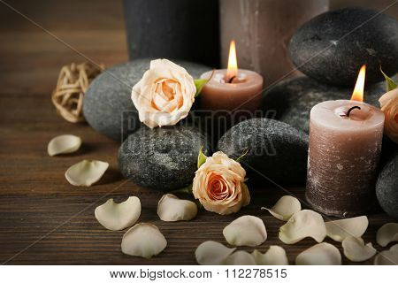 Beautiful relax composition of alight candles, pebbles and flowers on wooden background
