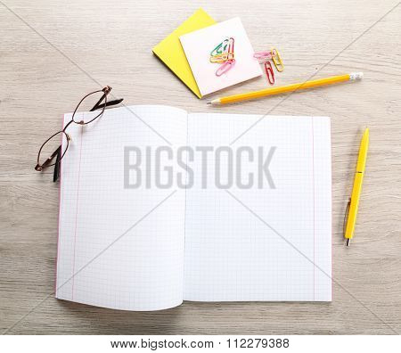 Opened checked notebook with stationery on grey wooden background