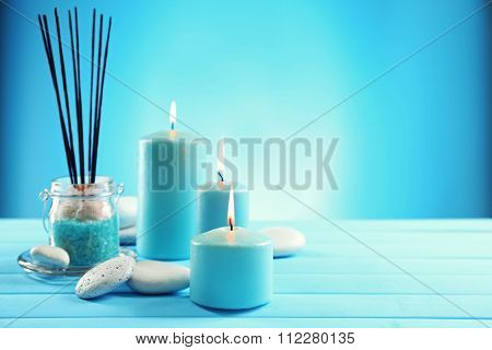 Spa composition of blue candles, stones and sea salt on blue background