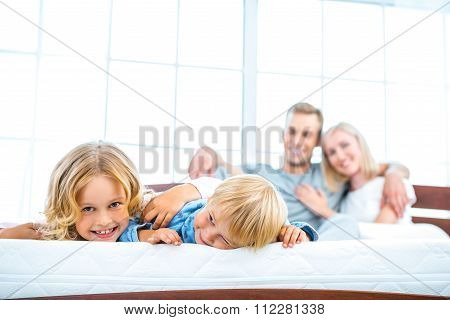 Young family lying on white bed