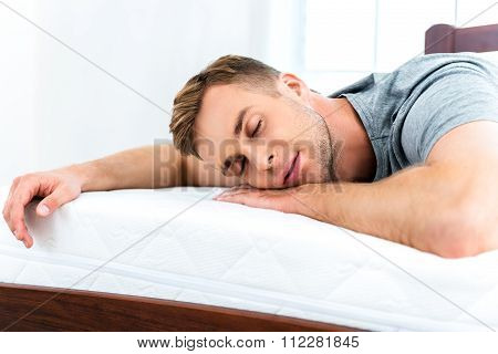 Young man sleeping on white bed