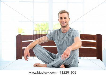 Young man sitting on white bed