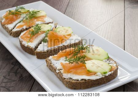 Sandwiches with salmon, ricotta, dill and cucumber on a wooden background. On background platter wit