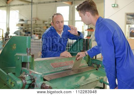 Engineer talking to apprentice over machine