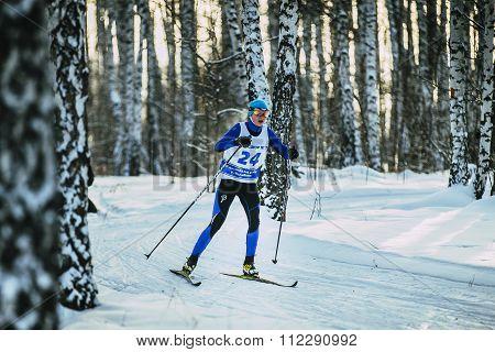 girl skier race classic style in birch forest in winter