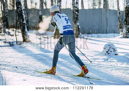 male athlete skier during race forest classic style. vapor when breathing