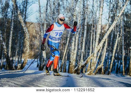 young male athlete skiers race in winter forest classic style riding uphill