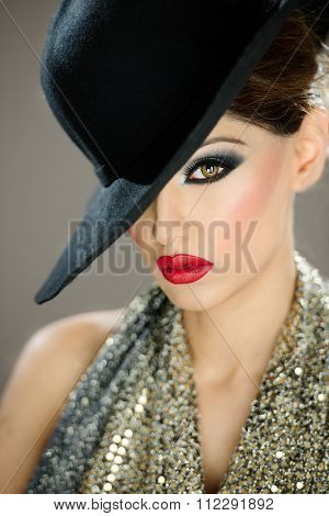 Beautiful female model with makeup wearing a hat with red lips