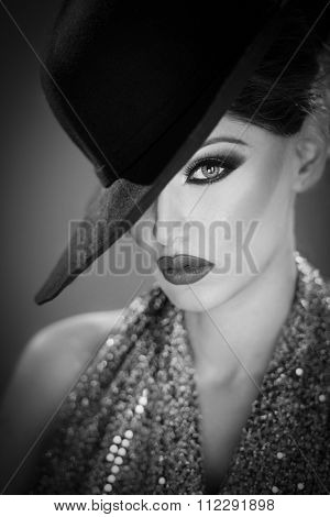 Beautiful female model with makeup wearing a hat in black and white