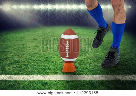 American football player being about to kick ball against rugby pitch