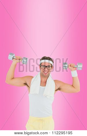 Geeky hipster lifting dumbbells in sportswear against pink