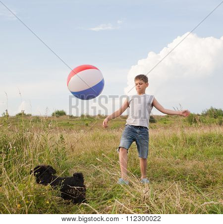Young Boy Playing With A Ball Outdoors