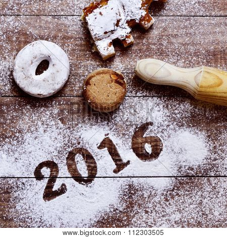 high-angle shot of a wooden table sprinkled with icing sugar where you can read the number 2016, as the new year, and some different pastries and a rolling pin