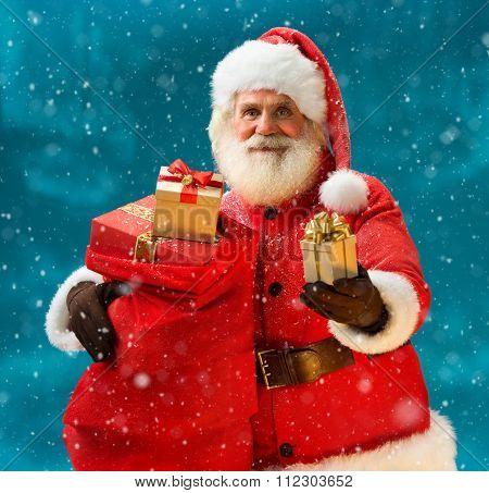 Santa Claus with christmas present and looking at camera