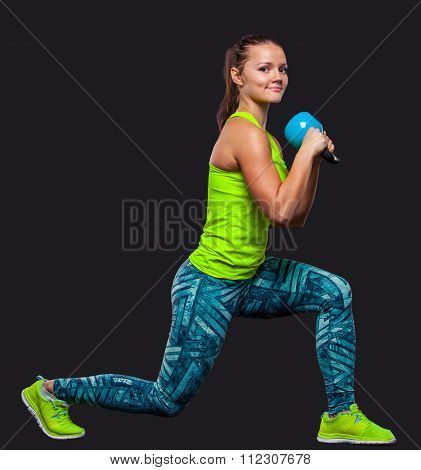 Young woman smiling while using kettlebells against a gray background