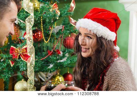 Beautiful Girl In Santa Hat Looking At Guy On Christmas