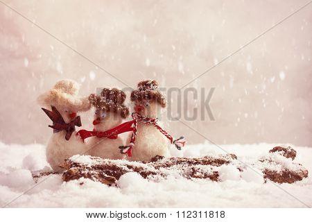 Snowmen having a gossip on a snow covered log