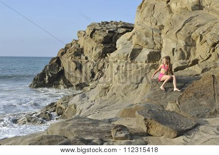 A Girl In Pink Swimming Costume On The Rocky Beach.