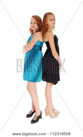 Two Girls In Dresses Standing Back To Back.