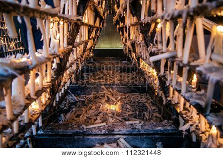 Offerings of candles in the pilgrimage of Rocio. Lighted candles on the shelf. A candle fell from sh