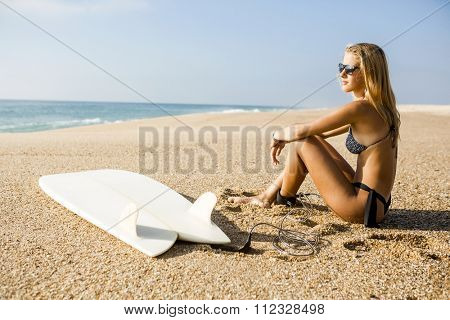 Beautiful surfer girl sitting on the beach and checking the waves