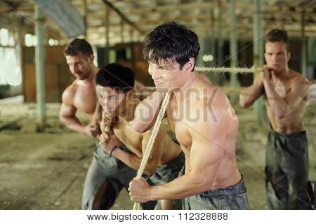 Four young guys are dragging something ropes in abandoned building man in the foreground in focus