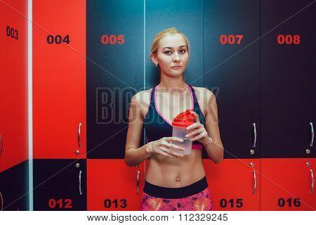 Before training. Girl in a gym locker room