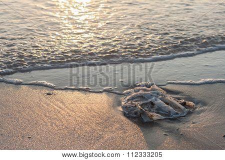 Used plastic bag garbage on sand beach