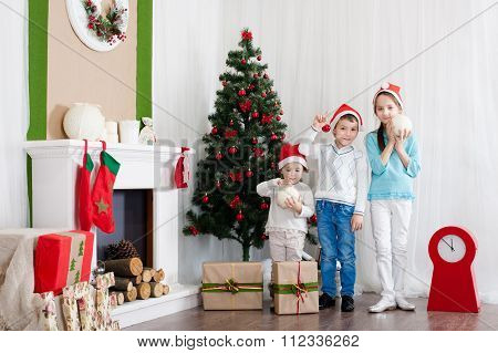 Children are kept New Year's toys near Christmas tree and fireplace