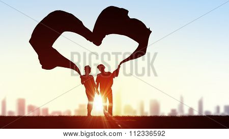 Silhouettes of guy and girl representing love and affection on sunset background