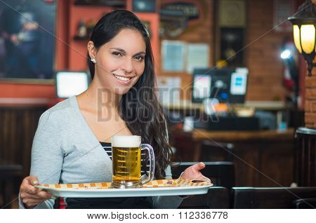 Brunette model waitress at restaurant smiling happily carrying a tray with glass fo beer on it
