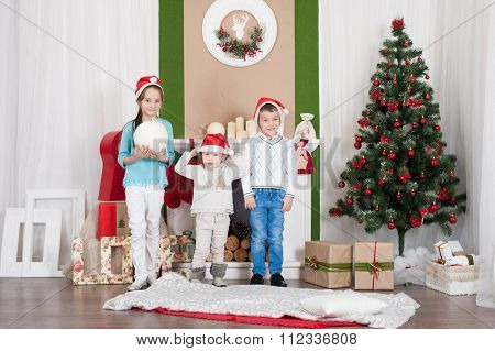 smiling children next to Christmas tree and fireplace