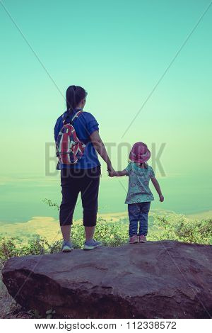 Mother And Daughter Standing On Boulder And Clasping Hand Together.