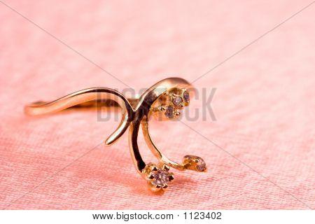 Anillo de oro en pliegues de seda color de rosa