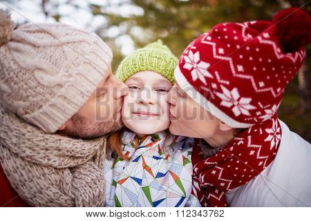 Mother and father giving a kiss to their daughter outdoors