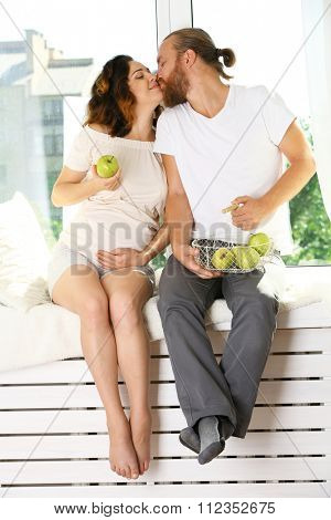 Happy beloved couple in waiting for baby's birth on window board with apples