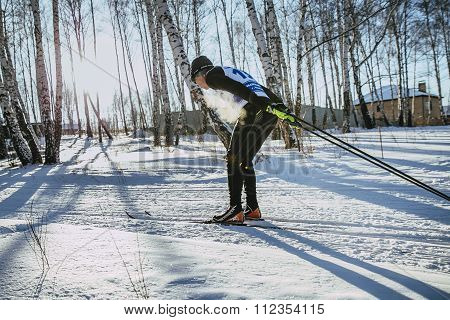 young male skier of classic style in winter woods on sports race, vapor when breathing